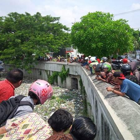 Hindari Razia Lalu lintas, Seorang Pengendara Motor Nekat terjun ke Sungai Penuh Sampah Di Surabaya