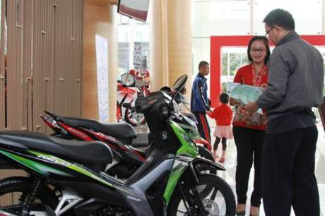 Sales Honda menjelaskan teknologi sepeda motor New Honda Revo FI kepada konsumen. AHM semakin memperkuat predikat Rajanya Motor Bebek melalui penjualan motor bebek yang tercatat sebanyak 218.639 unit atau memimpin 45% pangsa pasar motor bebek nasional.